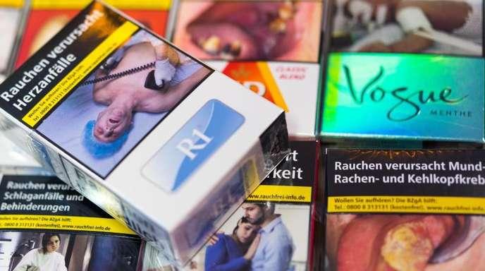 Zigarettenschachteln mit Schockbildern liegen auf einem Tresen in einem Kiosk.