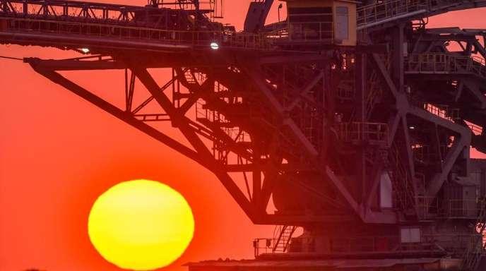 Die aufgehende Sonne hinter einem Absetzer für Abraum am Rande des Braunkohletagebaus Jänschwalde der Lausitz Energie Bergbau AG (LEAG).