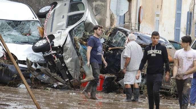 Einwohner von Sant Llorenc des Cardassar gehen nach dem schweren Unwetter an Autowracks vorbei.