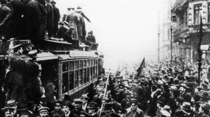Streikende Arbeiter füllen am 9. November 1918 die Straßen von Berlin. Kurz darauf verkündet Philipp Scheidemann die Republik.