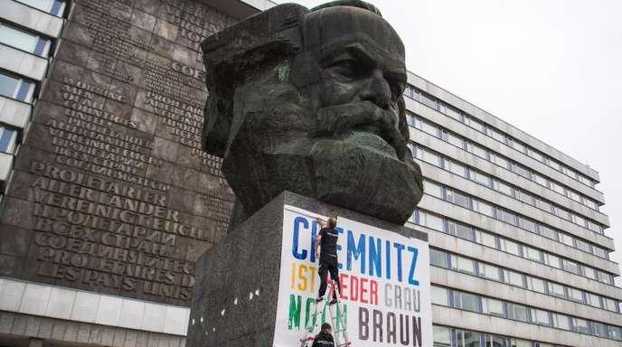 1. September: Zwei Männer befestigen am Karl-Marx-Denkmal ein Plakat mit der Aufschrift «Chemnitz ist weder grau noch braun».