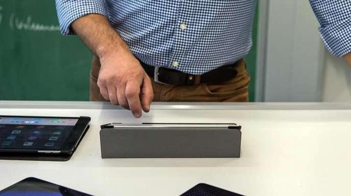Ein Lehrer bedient in einem Klassenzimmer in einer Schule einen Tabletcomputer.