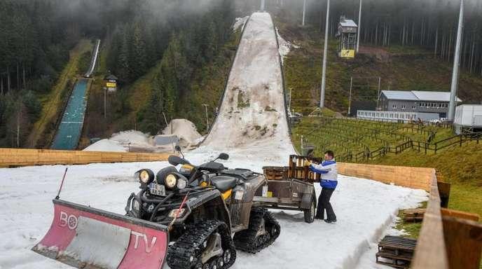 Der Hang der Skisprungschanze im Schwarzwald sieht aus wie ein Schlachtfeld: Grüne und graue Flecken, Matsch, Dreck und ein Rest von Kunstschnee.