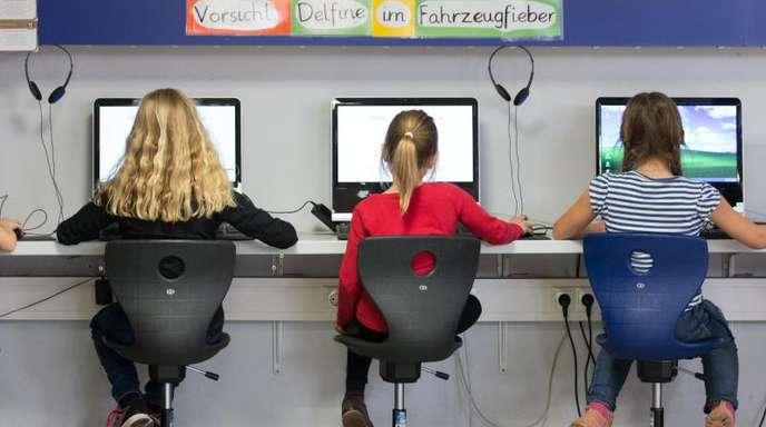 Schüler arbeiten in einem Klassenraum einer Grundschule an Computern.