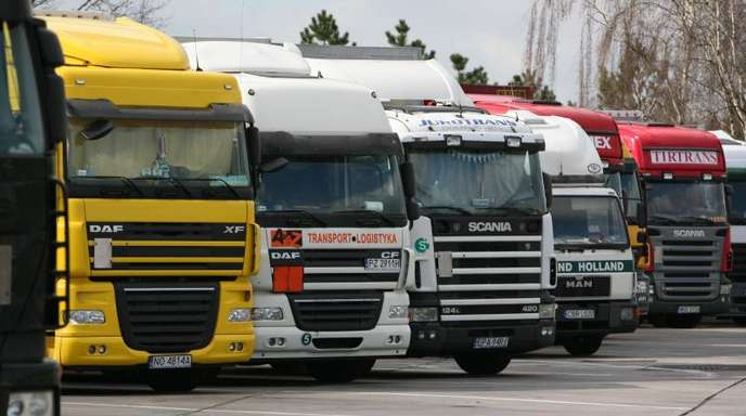 Verchiedene Lastwagen parken an einer Raststätte.