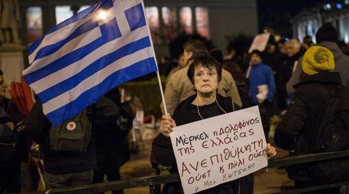 Eine Frau hält aus Protest gegen den Besuch von Bundeskanzlerin Merkel ein Schild mit der Aufschrift «Merkel, die Mörderin Griechenlands - unerwünscht».