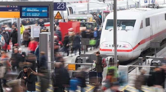 Reisende gehen am Hauptbahnhof über eine Plattform.