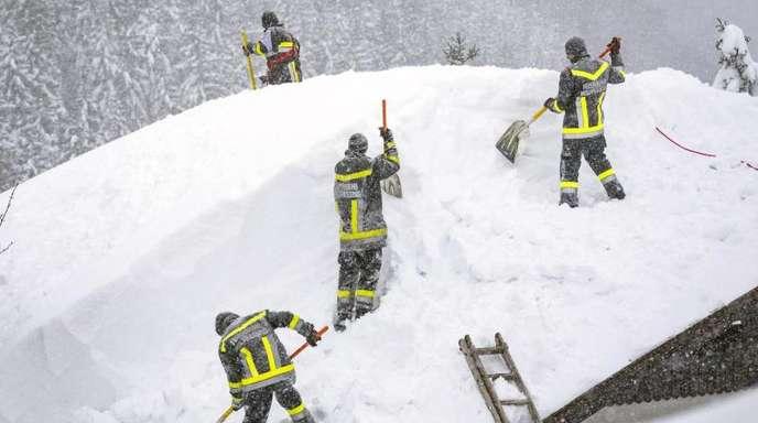 Feuerwehleute räumen den Schnee von einem Dach im österreichischen Annaberg.
