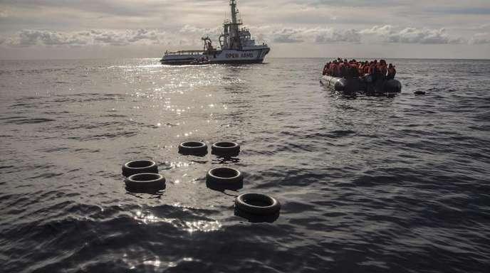 Migranten sitzen in einem Schlauchboot, nachdem sie im Mittelmeer entdeckt und gerettet wurden.