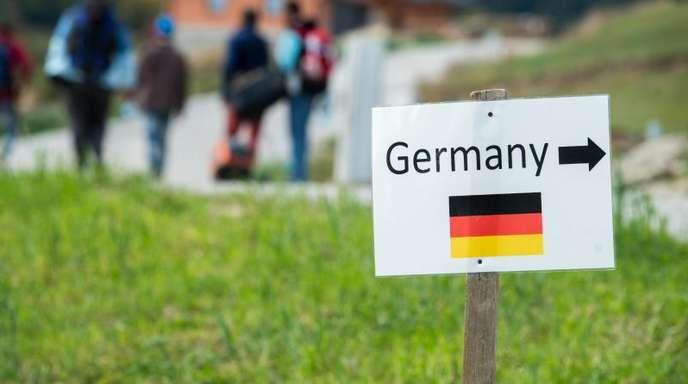 Ein Schild weist Flüchtlingen im Herbst 2015 den Weg zur deutschen Grenze.