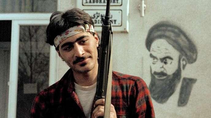 Ein Chomeini-Anhänger hält ein Gewehr mit einer roten Nelke.