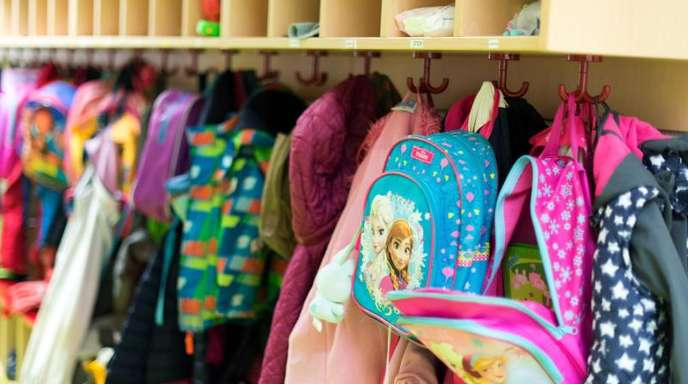 Kinderjacken und Rucksäcke hängen in einer Kindertagesstätte. Wie die Bundesländer das Geld aus dem «Gute-Kita-Gesetz» einsetzen, können sie selbst entscheiden - sie müssen aber Verträge mit dem Bund schließen.