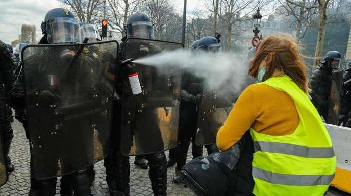 Französische Polizisten verwenden in Paris Pfefferspray gegen eine «Gelbwesten»-Demonstrantin.