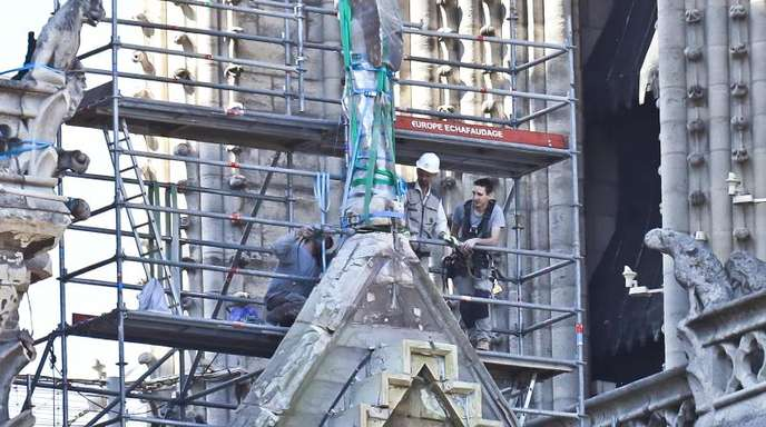 Arbeiter bereiten eine Statue auf einem Dach von Notre-Dame auf die Demontage durch einen Kran vor.