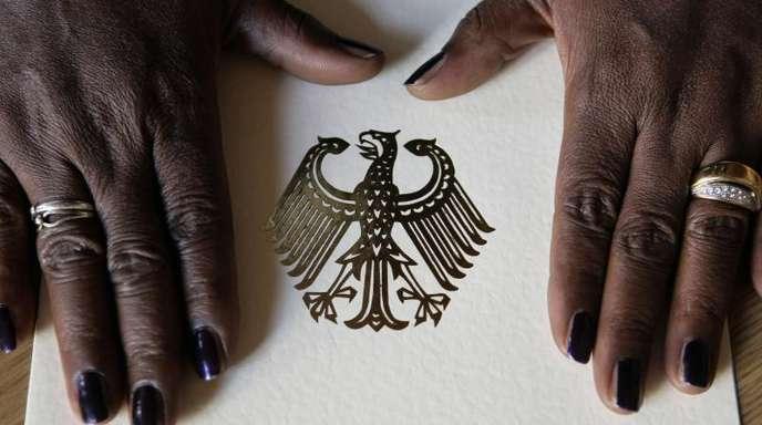 Hände einer dunkelhäutigen Frau auf der Einbürgerungsurkunde der Bundesrepublik Deutschland.