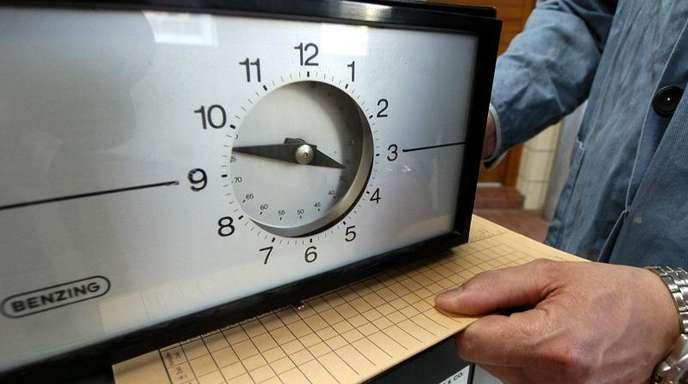 Eine Karte zur Arbeitszeiterfassung und eine Stechuhr. Nach einem Urteil des EuGH sollen Arbeitgeber die Arbeitszeiten ihrer Beschäftigten systematisch erfassen.
