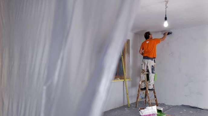 Ein Maler spachtelt die Wände eines Zimmers.