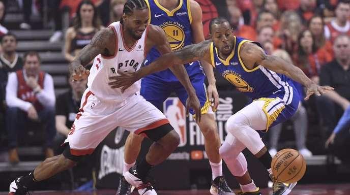 Raptors-Star Kawhi Leonard (l) im Kampf um den Ball mit Andre Iguodala (r) von den Warriors.