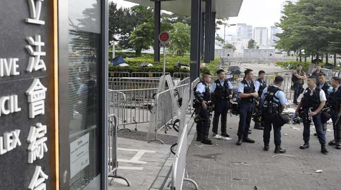 Polizeibeamte stehen vor dem Legislativrat Wache. In der Nacht zuvor war es zu gewaltsamen Zusammenstößen mit Demonstranten gekommen.
