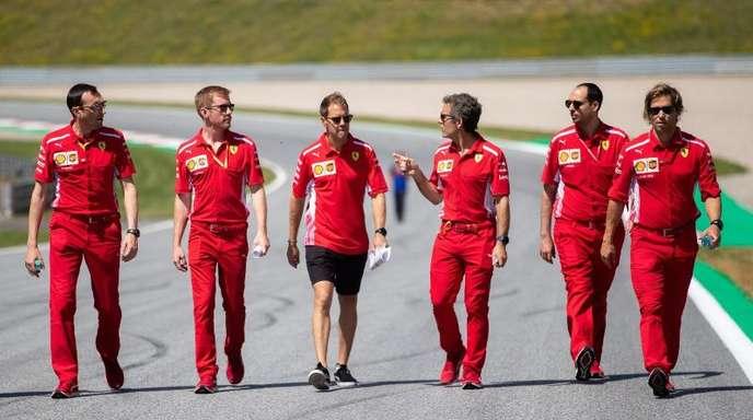 Sebastian Vettel (M) geht mit seinem Team die Rennstrecke in Spielberg ab.