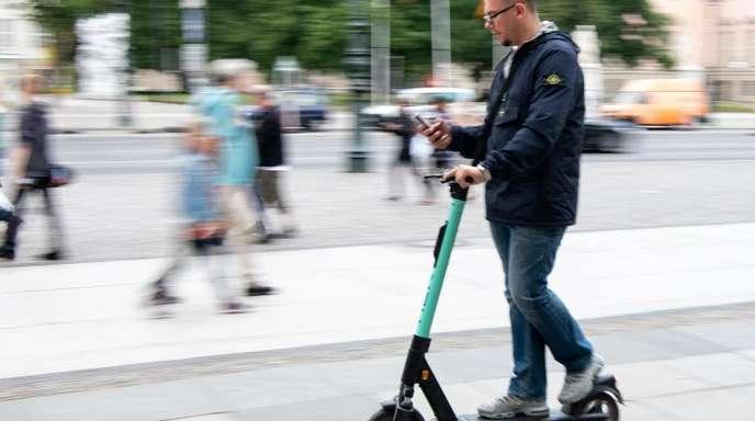 Auf zwei winzigen Rädern im Innenstadtverkehr, die Augen fest aufs Handy geheftet: Ein Tourist fährt durch Berlin-Mitte.