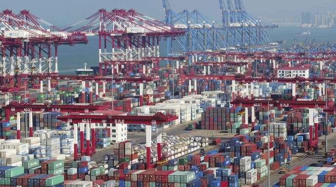 In einem Hafen stehen Container und Containerbrücken. Der Handelskrieg mit den USA setzt Chinas Wirtschaft kräftig zu.