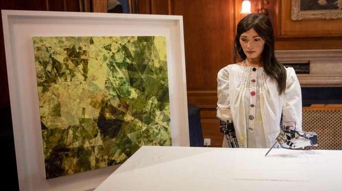 Ai-Da, die weltweit erste Roboterkünstlerin, in Oxford neben einem eigenen Kunstwerk.