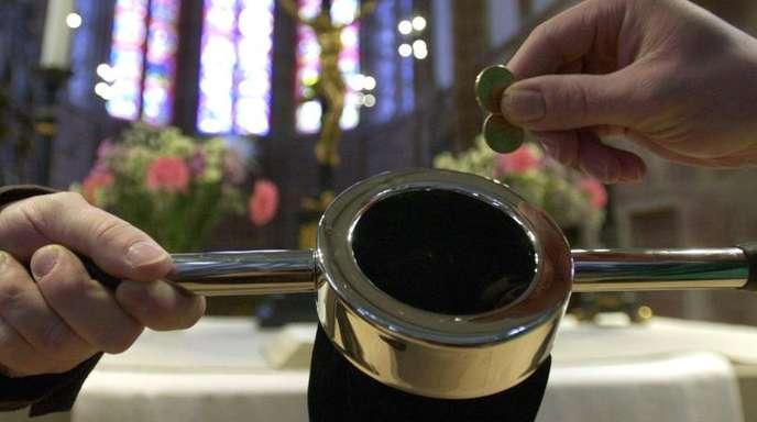 Ein Kirchenbesucher (r) steckt einige Münzen in einen Klingelbeutel.