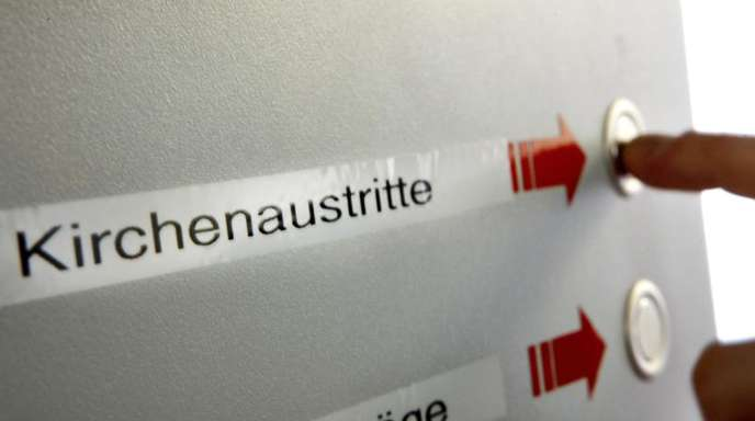 Eine Wartenummer für den Antrag auf den Austritt aus der Kirche drückt eine Frau beim Amtsgericht Köln.