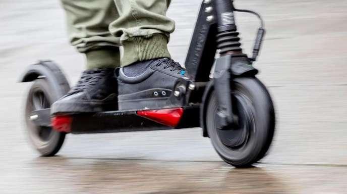 Ein Mann fährt mit einem E-Scooter auf dem Gehweg.