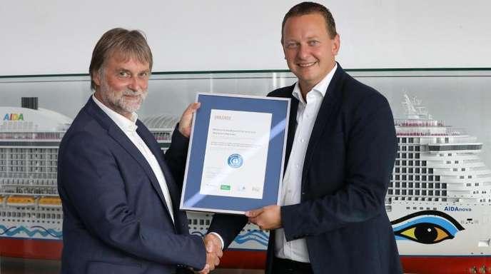 Ralf-Rainer Braun (l), Vorsitzender der Jury Umweltzeichen, überreicht Felix Eichhorn, Präsident von Aida Cruises, die Urkunde «Blauer Engel».