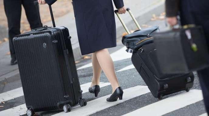 Eine Flugbegleiterin ist unterwegs zum Flughafen.
