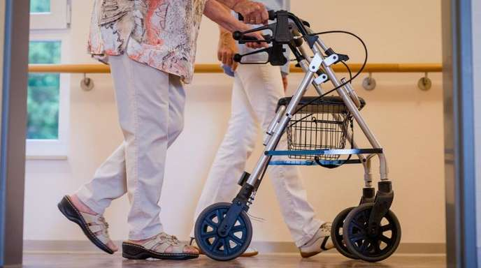 Eine Pflegekraft in einem Pflegeheim mit einer älteren Dame.