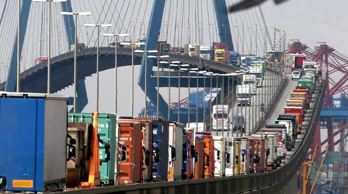 Mit Containern beladene Lastwagen stauen sich auf der Köhlbrandbrücke im Hafen Hamburg.