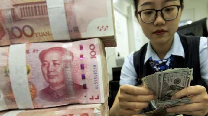 Ein Stapel Yuan-Banknoten: Chinas Notenbank stemmt sich gegen die schwächelnde Wirtschaft der Volksrepublik.