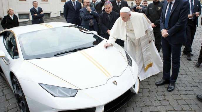 Papst Franziskus signiert den weißen Lamborghini, der ihm vom italienischen Sportwagenhersteller geschenkt wurde.