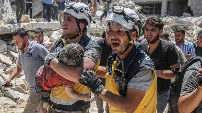 Weißhelme des syrischen Zivilschutzes tragen ein verletztes Kind aus den Trümmern eines zerstörten Gebäudes in der Provinz Idlib.
