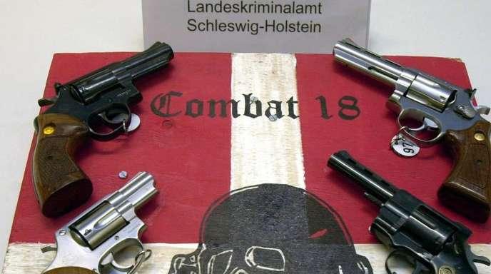 Sichergestellte Waffen und ein Schild der Neonazi-Gruppe «Combat 18» im schleswig-holsteinischen Landeskriminalamt.