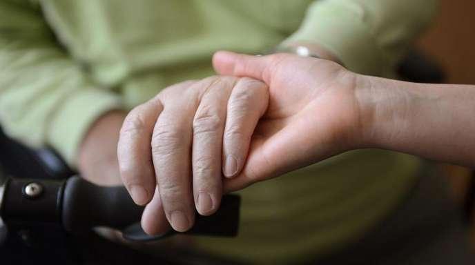 Eine junge Frau hält die Hände eines alten Mannes.
