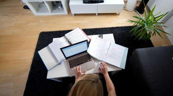 Zu Hause statt im Büro:Eine Frau arbeitet in einem Wohnzimmer an einem Laptop.
