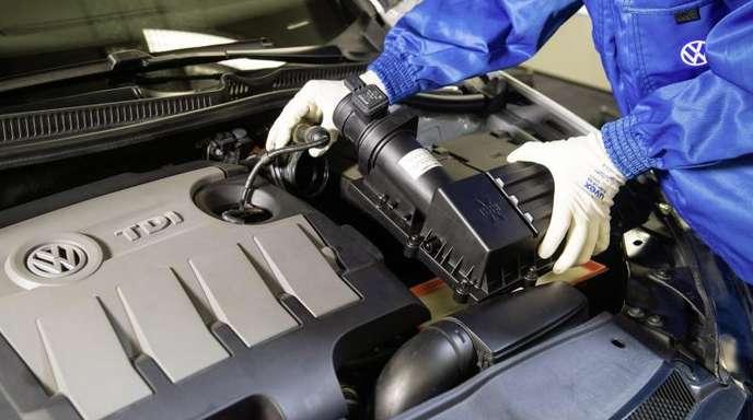 Ein VW-Mitarbeiter baut einen um einen Strömungsgleichrichter erweiterten Luftfilter in einen Dieselmotor der Typreihe EA 189 ein.