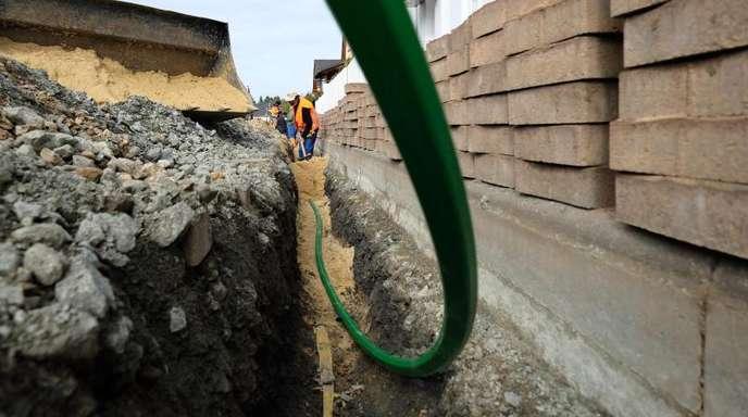 Bauarbeiter bereiten die Verlegung von Glasfaserkabeln in einem Wohngebiet vor.