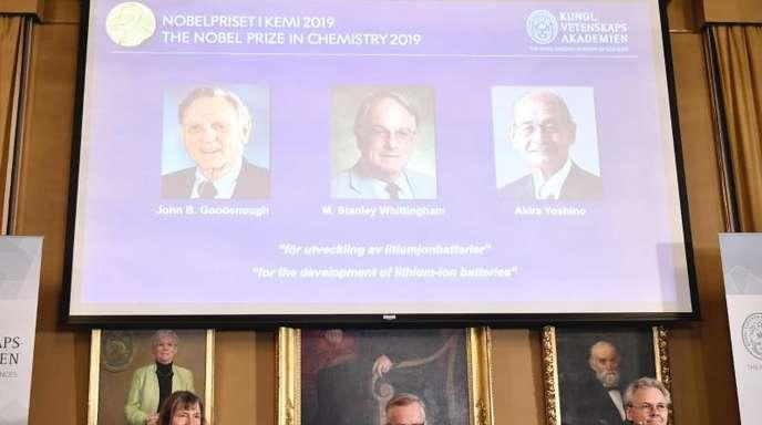 Goran K. Hansson (M) Generalsekretär der Königlich Schwedischen Akademie der Wissenschaften, und die Akademiemitglieder, Sara Snogerup Linse (l) und Olof Ramstrom verkünden die Gewinner des Chemie-Nobelpreises 2019, die auf der Leinwand gezeigt werden,