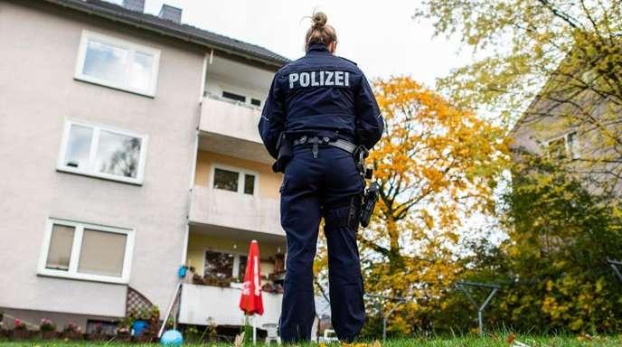 Eine Polizistin vor dem Mehrfamilienhaus in Detmold, in dem eine 15-Jährige ihren dreijährigen Halbbruder erstochen haben soll.