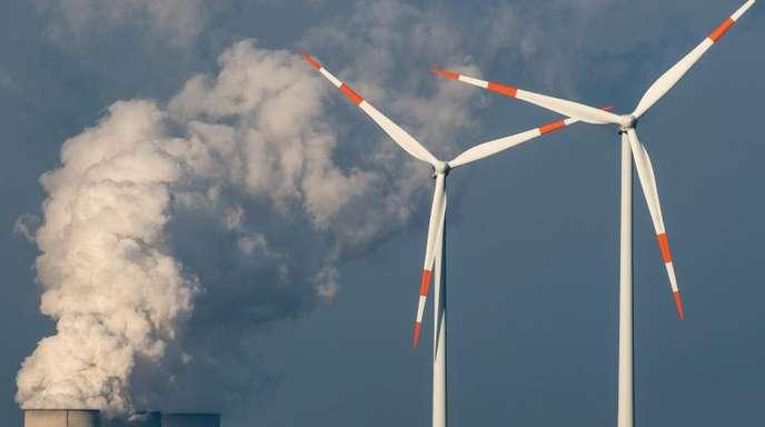 Windräder drehen sich vor den Kühltürmen des Braunkohlekraftwerkes in Jänschwalde (Brandenburg).