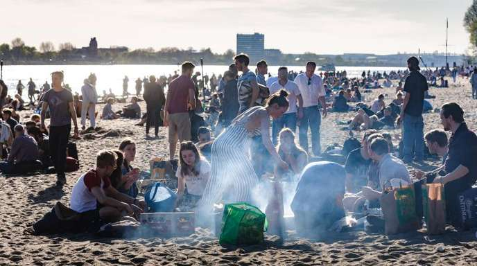 Hier sind Grillschalen aus Aluminium alltäglich:Menschen brutzeln am Elbstrand im Hamburg.