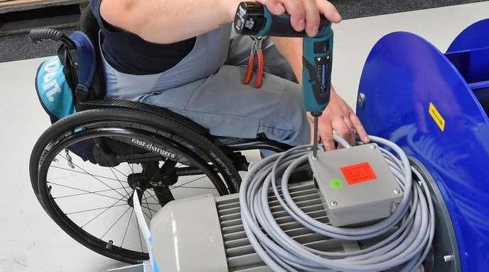 An einem Arbeitsplatz für Motorklemmen ist ein Mitarbeiter im Rollstuhl mit Montagearbeiten beschäftigt.