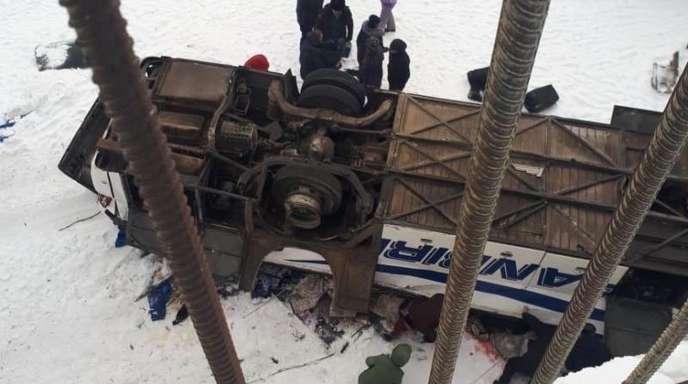 Der von einer Brücke gestürzte Bus liegt auf dem zugefrorenen Fluss.