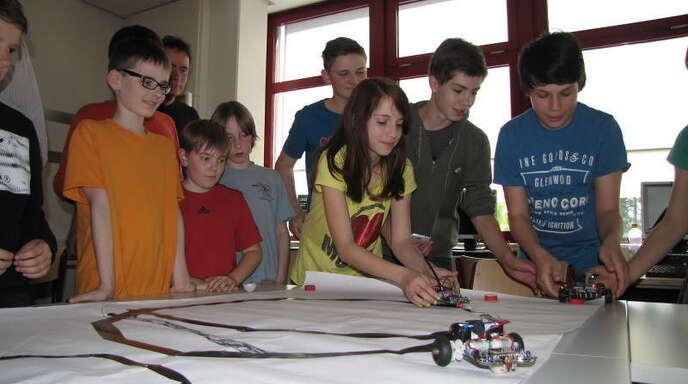 Die Mädchen und Jungen der Roboter AG probieren aus, ob sie ihren Roboter richtig programmiert haben und dieser auf der schwarzen Linie entlangfährt.