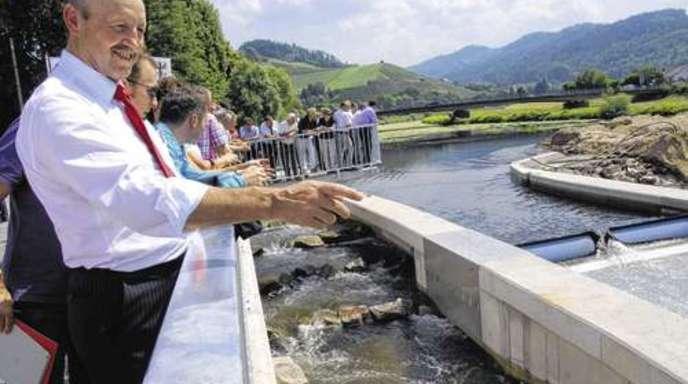 Projektleiter Georg Schmid (oben links) zeigt an der Fischtreppe auf den Bereich, wo sich die Turbine befindet